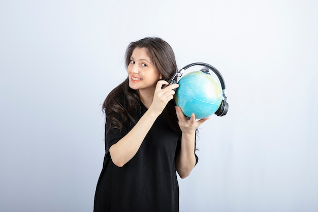 Lächelnde schöne junge frau, die einen globus in den kopfhörern steht und hält.
