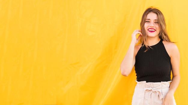 Lächelnde schöne junge frau, die in der front des gelben hintergrundes steht
