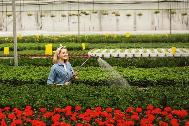 Lächelnde schöne junge frau, die in der orangerie und in den bewässerungsanlagen steht