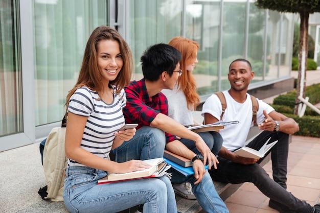 Lächelnde schöne junge frau, die mit ihren freunden sitzt und draußen handy benutzt