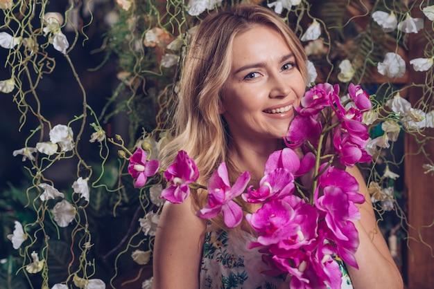 Lächelnde schöne junge frau, die niederlassung von rosa orchideen hält