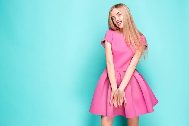 Lächelnde schöne junge frau im rosa minikleid posiert