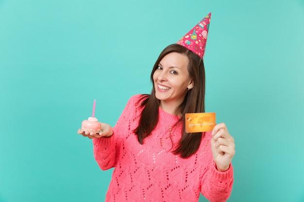 Lächelnde schöne junge frau in gestricktem rosa pullover, geburtstagshut in der hand halten kuchen mit kerze, kreditkarte isoliert auf blau-türkisfarbenem wandhintergrund. menschen lifestyle-konzept. kopieren sie platz.