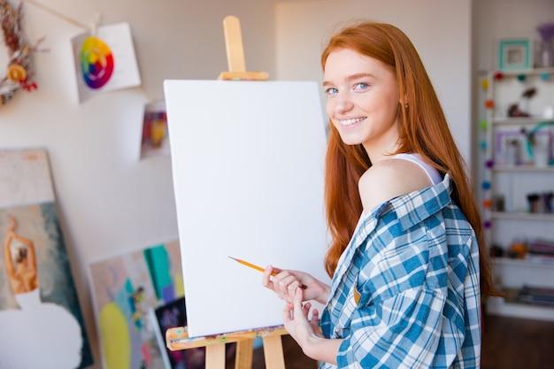 Lächelnde schöne junge malerin mit langen roten haaren, die in der künstlerwerkstatt shetches auf leerer leinwand macht