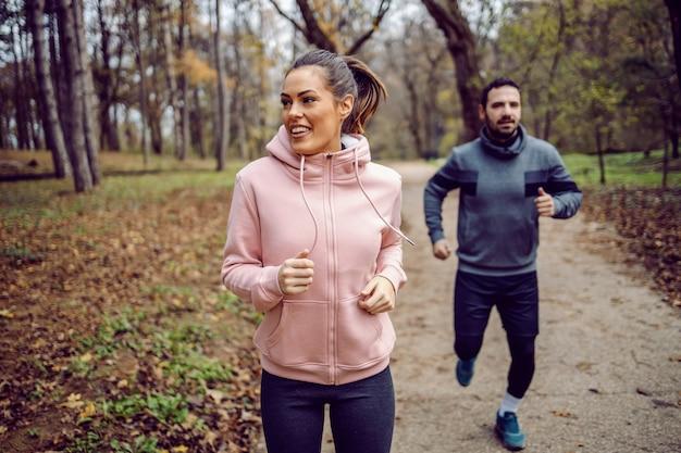 Lächelnde schöne kaukasische brünette in sportbekleidung, die ihren freund rast und gewinnt. laufen in der natur.
