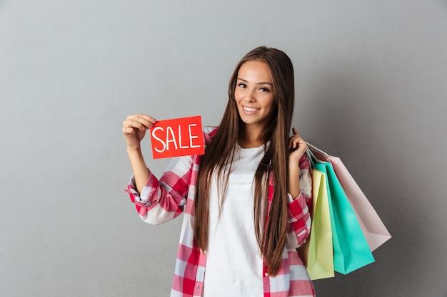 Lächelnde schöne kaukasische frau, die verkaufsschild und einkaufstaschen hält
