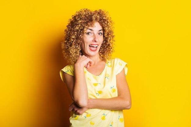 Lächelnde schöne lockige junge frau auf einem hellen gelben hintergrund