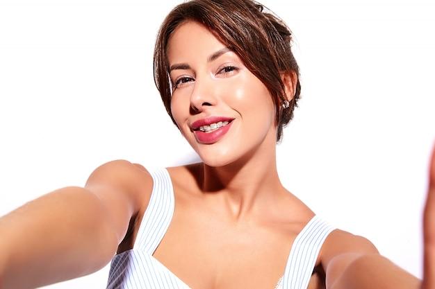 Lächelnde schöne niedliche brünette frau modell im lässigen sommerkleid ohne make-up mit weißen zahnspangen auf zähnen machen selfie foto am telefon, isoliert