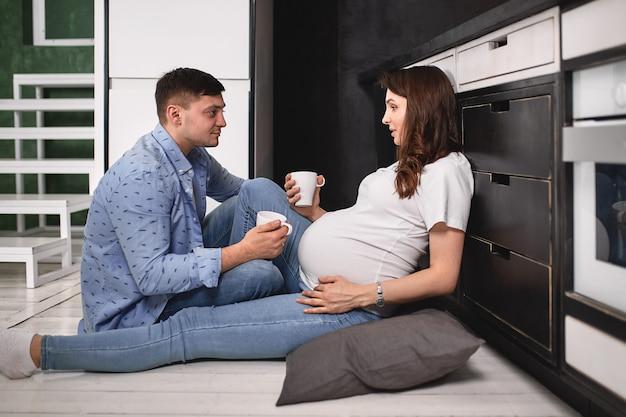 Lächelnde schöne schwangere frau und mann in der küche trinken kaffee und kochen.