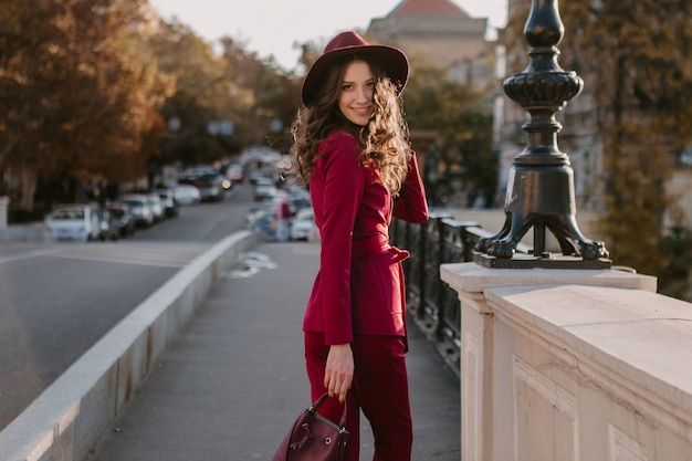 Lächelnde schöne stilvolle frau im lila anzug, der in der stadtstraße geht, frühlingssommer-herbstsaison-modetrend, der hut trägt, geldbörse hält
