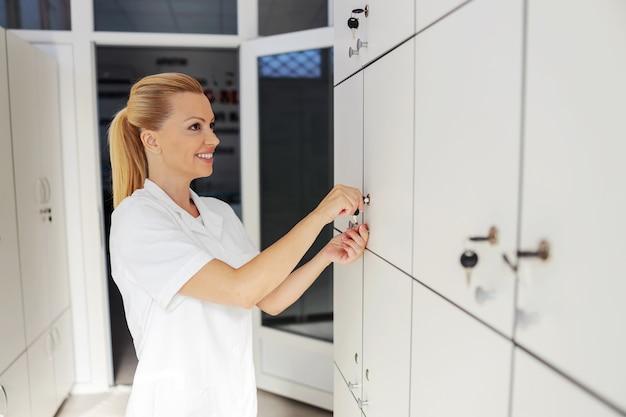 Lächelnde schöne weibliche blonde assistentin stehend und schließfach in der umkleidekabine aufschließend.