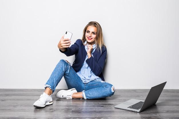 Lächelnde schönheits-studentin, die auf boden mit weißer wand und videoanruf auf handy mit glücklich sitzt, wenn sie laptop-computer-studie verwendet.
