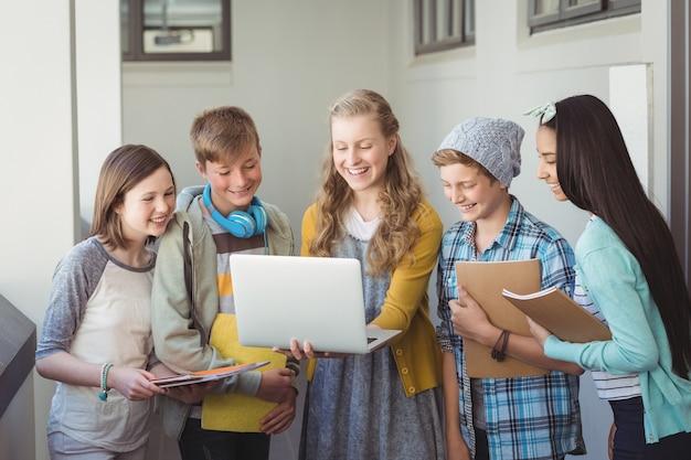 Lächelnde schüler, die laptop im korridor benutzen