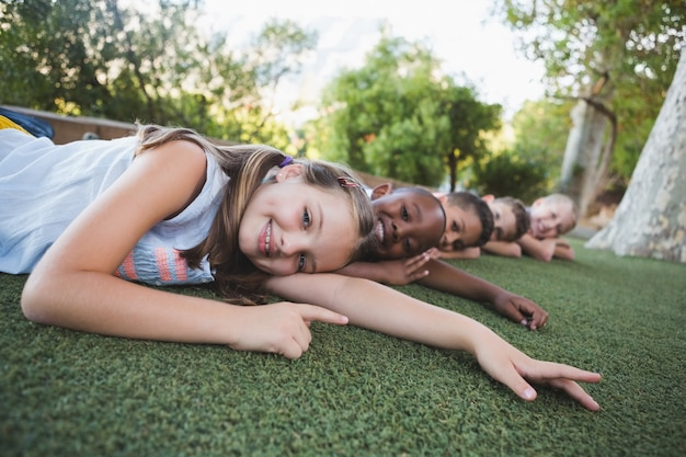 Lächelnde schulkinder, die auf gras im campus liegen