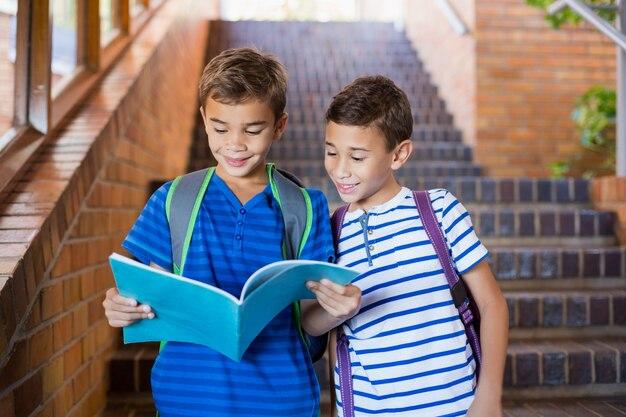 Lächelnde schulkinder, die ein buch auf treppenhaus lesen