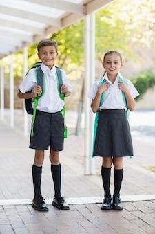 Lächelnde schulkinder, die im korridor stehen