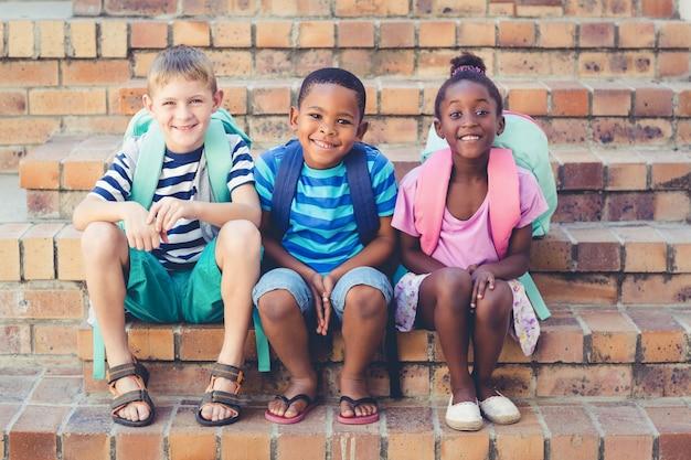Lächelnde schulkinder, die zusammen auf treppe sitzen