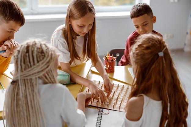 Lächelnde schulkinder, die zusammen geoboard im klassenzimmer verwenden