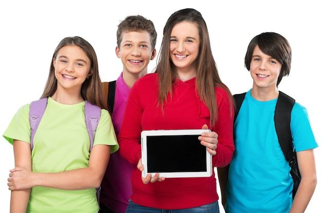 Lächelnde schulkinder mit rucksäcken und tablet