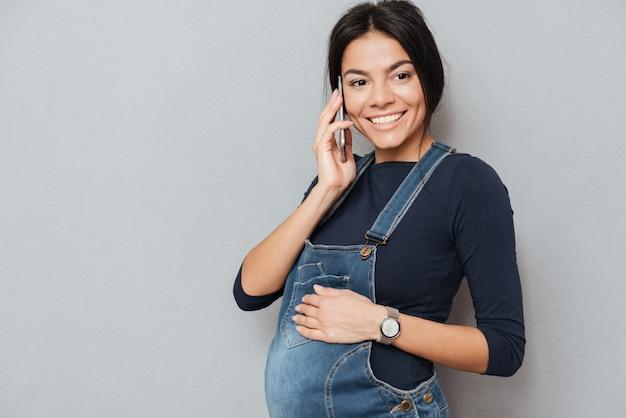 Lächelnde schwangere dame, die per telefon spricht.