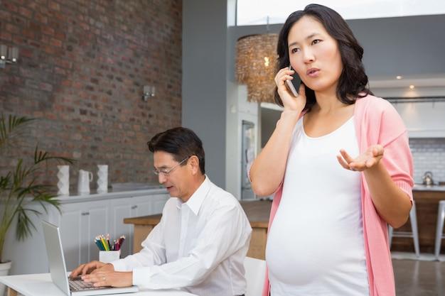 Lächelnde schwangere frau bei einem telefonanruf zu hause während ehemann, der an laptop arbeitet