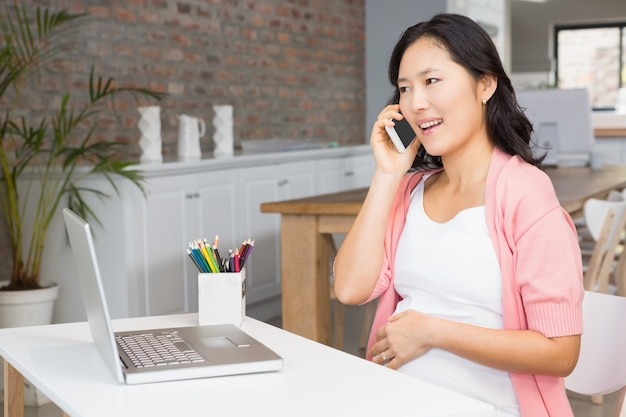 Lächelnde schwangere frau bei einem telefonanruf zu hause