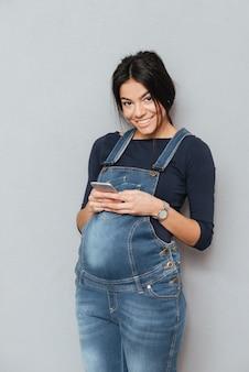 Lächelnde schwangere frau, die durch handy plaudert