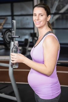 Lächelnde schwangere frau, die flasche wasser an der turnhalle hält
