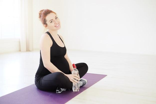 Lächelnde schwangere frau, die in yoga-haltung mit einer flasche wasser sitzt