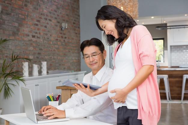 Lächelnde schwangere frau, die zu hause ihrem ehemann tablette zeigt