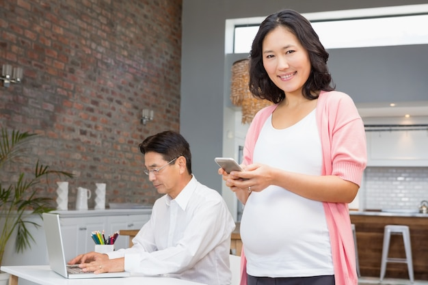 Lächelnde schwangere frau, die zu hause smartphone und ehemann arbeitet an laptop verwendet