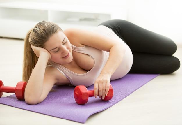 Lächelnde schwangere frau liegt auf fitnessmatte mit hanteln