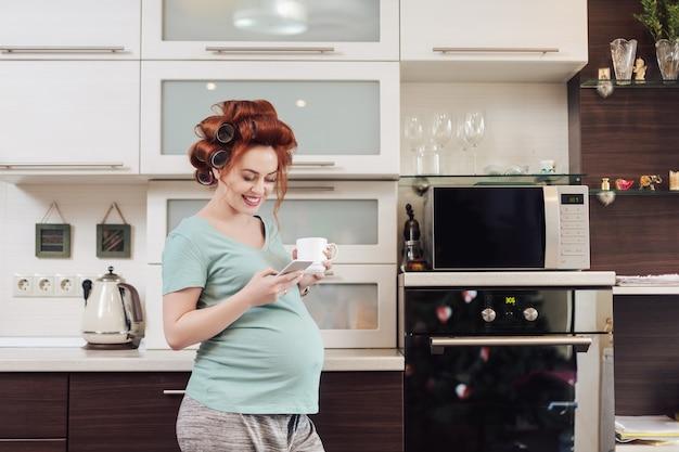 Lächelnde schwangere frau mit einem smartphone