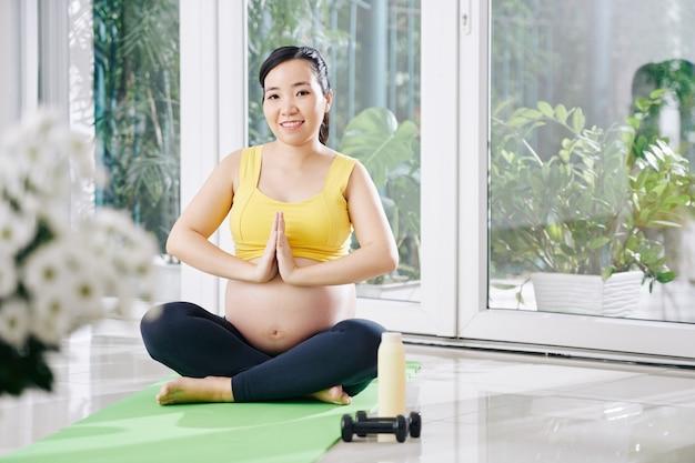 Lächelnde schwangere junge asiatische frau, die in lotussitz auf yogamatte sitzt und namaste geste macht