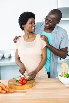 Lächelnde schwangere paare, die zu hause gemüse in der küche hacken