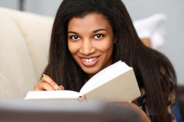 Lächelnde schwarze frau schreiben geschichte in notizbuch
