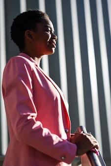 Lächelnde schwarze geschäftsfrau, die nahes geschäftslokalgebäude steht