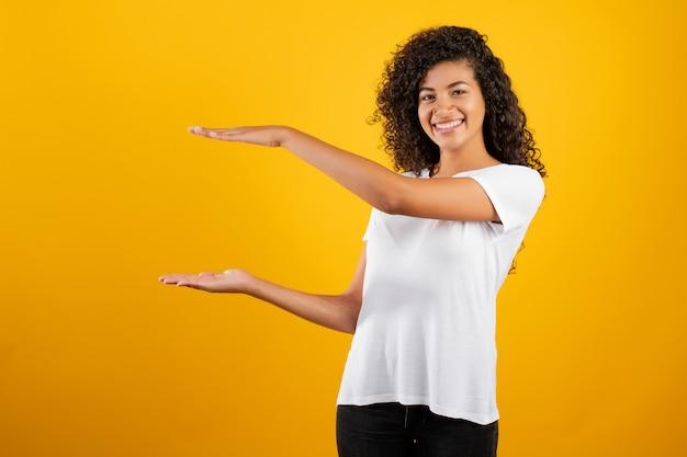Lächelnde schwarze schöne frau mit copyspace zwischen den händen getrennt über gelb
