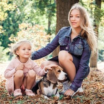 Lächelnde schwestern, die mit beagle-hund spielen