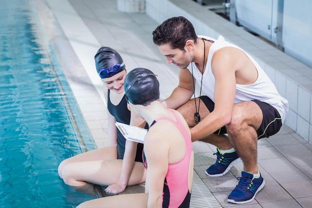 Lächelnde schwimmer, die klemmbrett in freizeitmitte betrachten