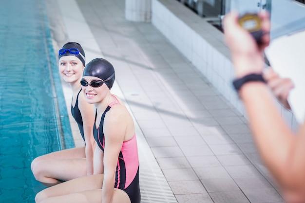 Lächelnde schwimmer, die trainer in der freizeitmitte betrachten
