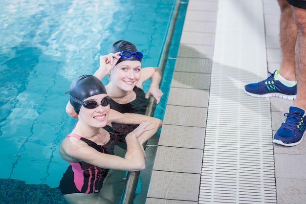Lächelnde schwimmer, welche die kamera in der freizeitmitte betrachten