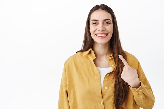 Lächelnde selbstbewusste frau, die mit stolzem, entschlossenem gesicht auf sich selbst zeigt, sich selbst fördert, ihre neuen weißen zähne zeigt und über der studiowand steht