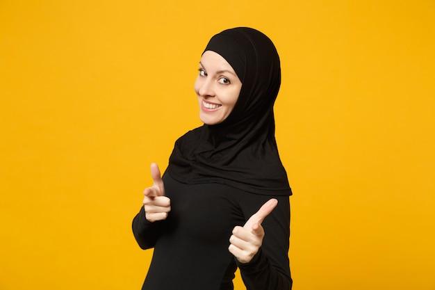 Lächelnde selbstbewusste schöne junge arabische muslimische frau in hijab schwarzer kleidung posiert isoliert auf gelber wand, porträt. menschen religiösen islam lifestyle-konzept.