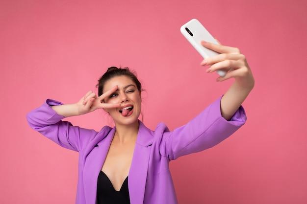 Lächelnde sexy frau in lila anzug, die ein selfie-foto auf dem handy macht, das zunge und friedensgeste-telefon einzeln auf rosafarbenem hintergrund mit blick auf das handy-display zeigt