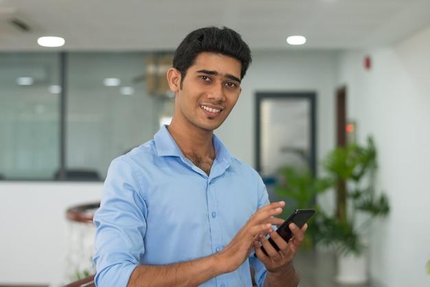 Lächelnde simsende mitteilung des büroangestellten am telefon
