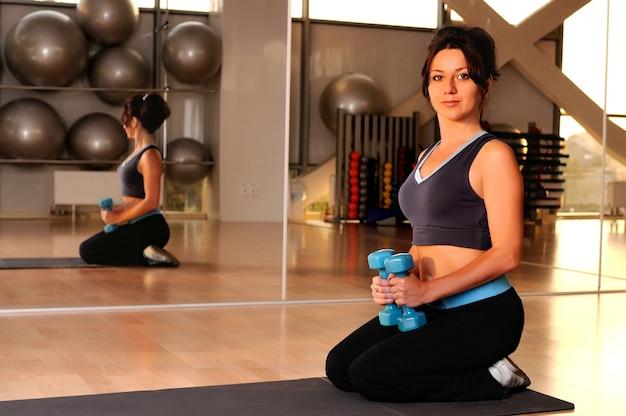 Lächelnde sitzende kaukasische weiße brünette frau mit hanteln in den händen auf yogamatte im fitnessstudio.