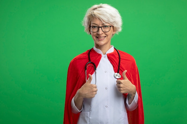 Lächelnde slawische superheldenfrau in arztuniform mit rotem umhang und stethoskop in optischen gläsern daumen hoch von zwei händen lokalisiert auf grüner wand mit kopienraum