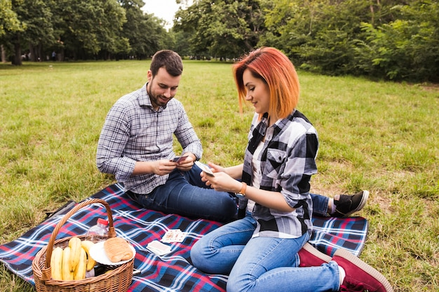Lächelnde spielkarten der jungen paare, die auf decke am picknick sitzen