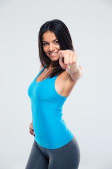 Lächelnde sportfrau, die finger auf kamera zeigt